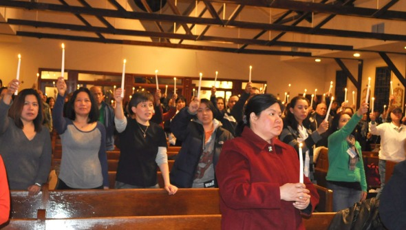 Filipino Americans light candles to express solidarity with the campaign to push for TPS designation for the Philippines during the forum at the Ascension Church in Queens.   Photo by NOEL T. PANGILINAN